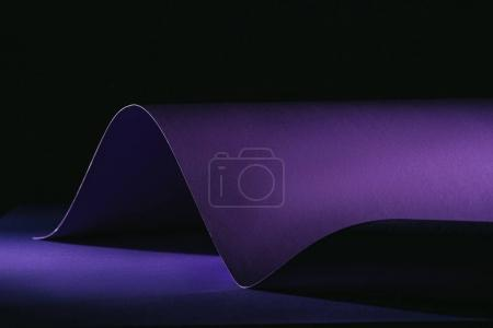 Photo for Warping purple paper on purple surface on black - Royalty Free Image