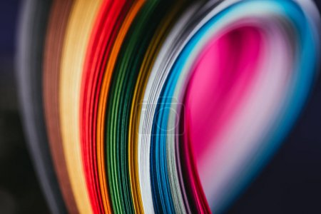 close up of colored bright quilling paper curves on black