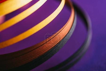 close up of yellow and black quilling paper curves on purple
