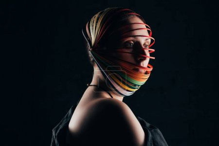 portrait of woman with colored quilling paper on head isolated on black