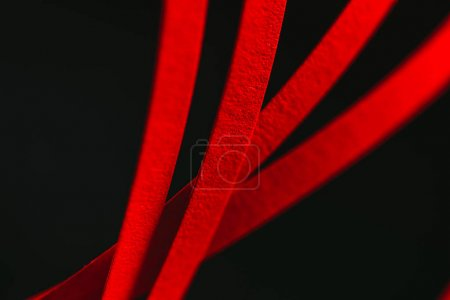 close up view of red quilling striped paper on black