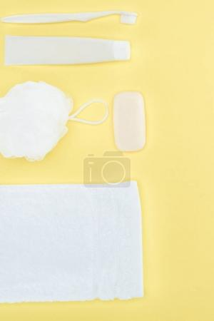 top view of toothbrush, toothpaste, towel, washcloth and soap, isolated on yellow