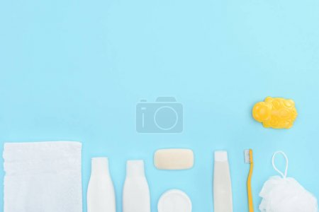 top view of toy, toothbrush, toothpaste, towel and soap, isolated on blue