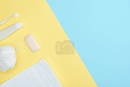 top view of toothbrush, toothpaste, towel, washcloth and soap, isolated on blue and yellow
