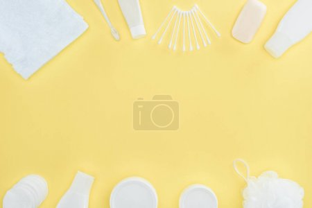 flat lay with cosmetic cream, body lotion, sponge, towel and cotton swabs, isolated on yellow