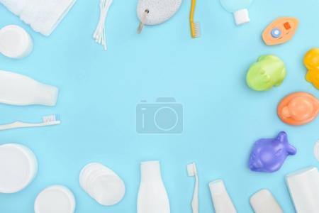 cropped view of cotton swabs, toothbrushes, bath toys, cosmetic cream and lotion in bottles, isolated on blue