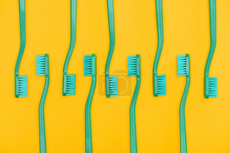 minimalistic background with green toothbrushes in row, isolated on yellow
