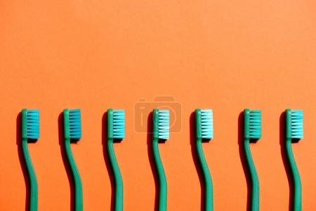 green toothbrushes in row, on orange with copy space
