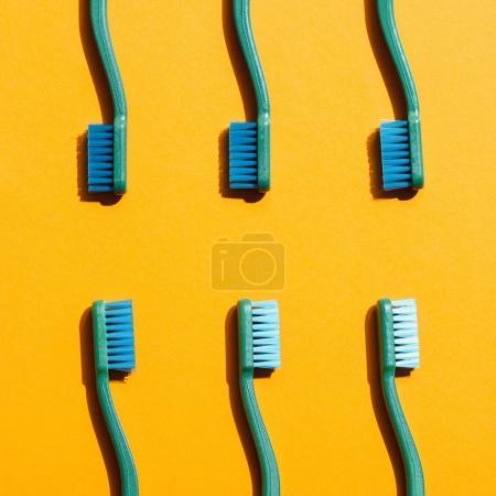 Photo pour Fond minimaliste avec brosses à dents vertes, sur fond jaune - image libre de droit