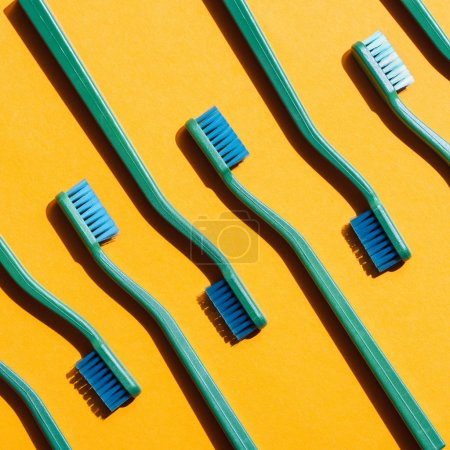 minimalistic background with green toothbrushes, on yellow