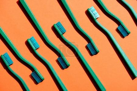 minimalistic background with green toothbrushes, on orange