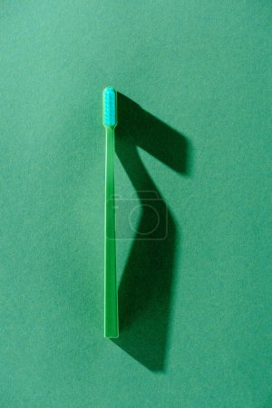 top view of one green toothbrush with shadow, on green