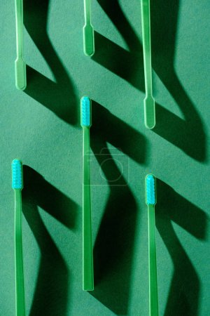 minimalistic background with green toothbrushes with shadows, on green