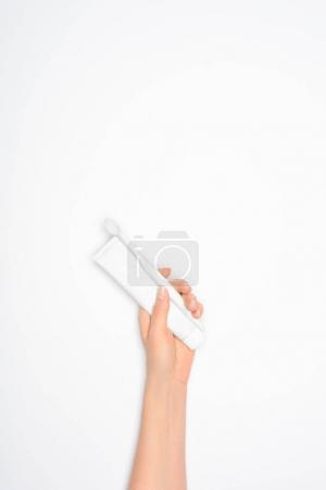Photo pour Vue recadrée de la femme tenant brosse à dents et dentifrice, isolée sur blanc - image libre de droit