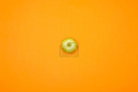 top view of green fresh apple, isolated on orange