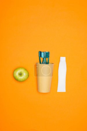 top view of apple, toothbrushes in paper cup and tube of toothpaste, isolated on orange