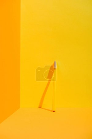 yellow toothbrush standing at orange wall