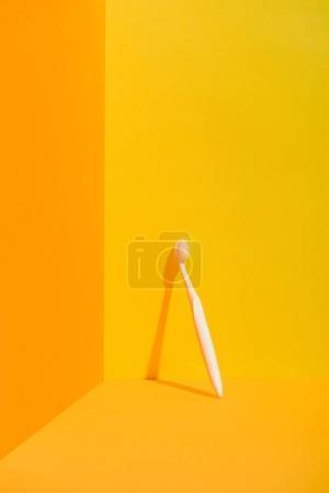 white toothbrush standing at orange wall