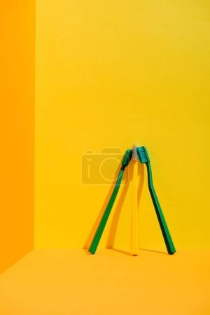 green and yellow toothbrushes at orange wall