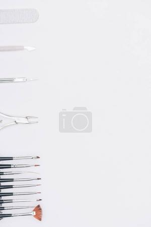 top view of brushes, scissors and nail nippers isolated on white