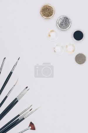 top view of brushes and glitter isolated on white