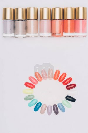 top view of row of nail polishes and palette isolated on white