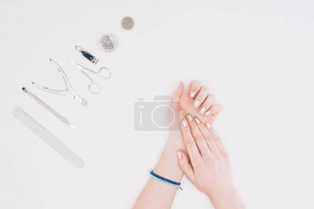 cropped image of female hands with silver manicure isolated on white