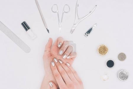 cropped image of female hands with silver nail polish isolated on white