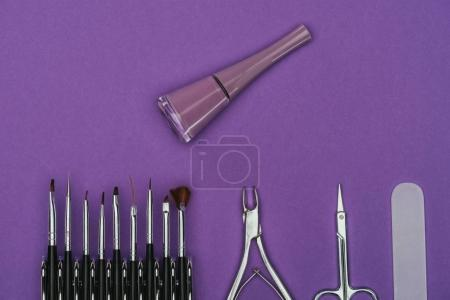 top view of nail polish and manicure tools isolated on purple