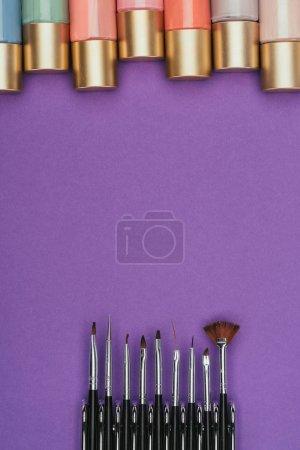 Photo pour Vue de dessus des vernis à ongles et des brosses isolés sur violet - image libre de droit