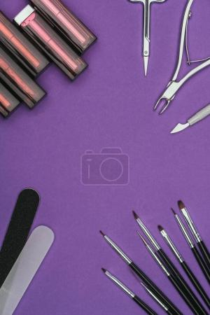 top view of lipsticks and manicure tools isolated on purple