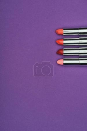 top view of red and pink lipsticks isolated on purple