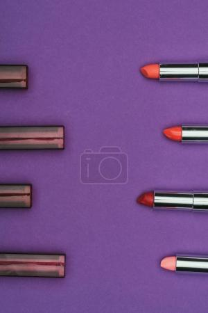 top view of colored lipsticks isolated on purple