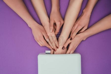 Photo for Cropped image of women putting girls hand into uv lamp isolated on purple - Royalty Free Image