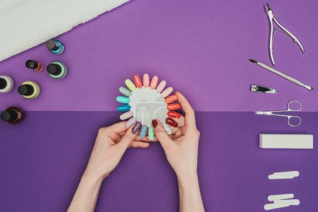 Photo for Cropped image of woman choosing color for nails with manicure palette - Royalty Free Image