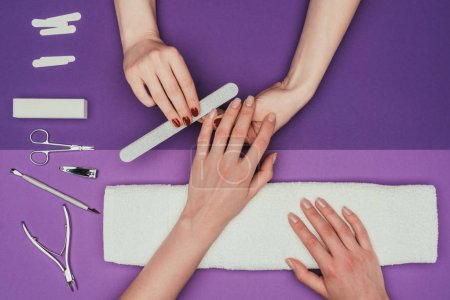 Photo for Cropped image of nail technician filing nails to customer with nail file - Royalty Free Image