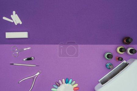 vista superior de herramientas de manicura y lámpara ultravioleta en mesa púrpura