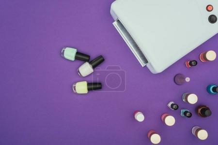 top view of different nail polishes and uv lamp isolated on purple