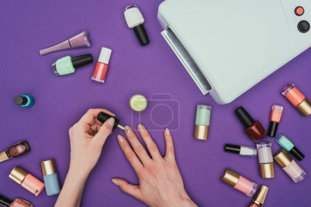 Photo for Cropped image of woman painting nails isolated on purple - Royalty Free Image