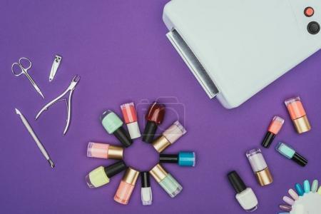 Photo pour Vue de dessus de la lampe UV et vernis à ongles isolés sur violet - image libre de droit