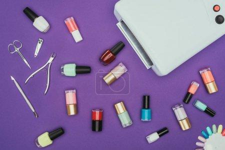 Photo pour Vue de dessus des vernis à ongles et lampe UV isolé sur violet - image libre de droit