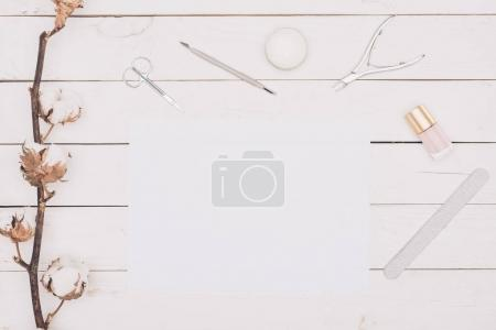top view of manicure tools and white paper on wooden table