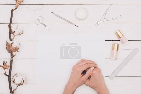 cropped image of woman sitting at table with manicure tools