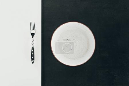 top view of steel fork and empty plate