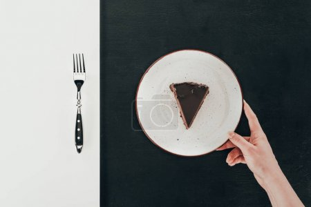 top view of woman holding plate with piece of cake on black background