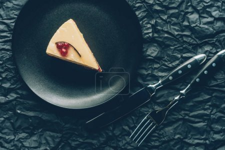 Photo for Top view of piece of cake on plate and cutlery on dark tabletop - Royalty Free Image