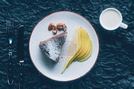top view of piece of cake with cutted pear on plate and cup of milk on dark tabletop