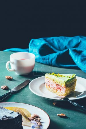 close up view of piece of cake on plate and cup of tea