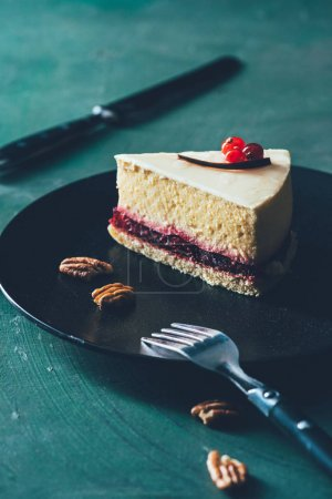 close up view of piece of cake on plate with hazelnuts and fork