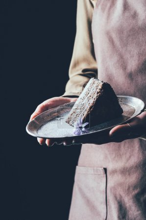 close up view of woman holding piece of homemade cake on plate in hands